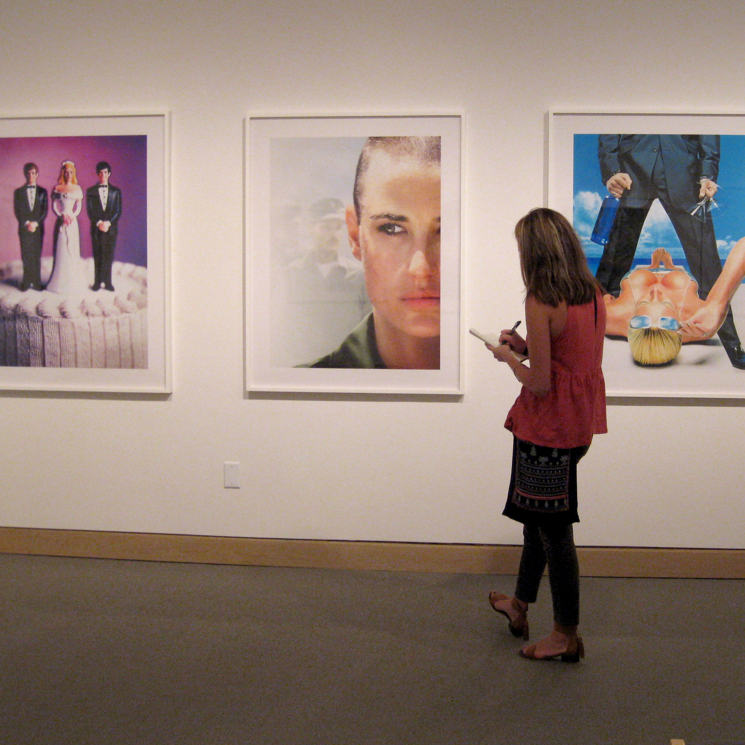 Photo of student in gallery looking at artwork