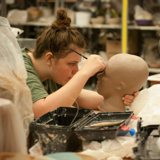 Photo of student refining clay head