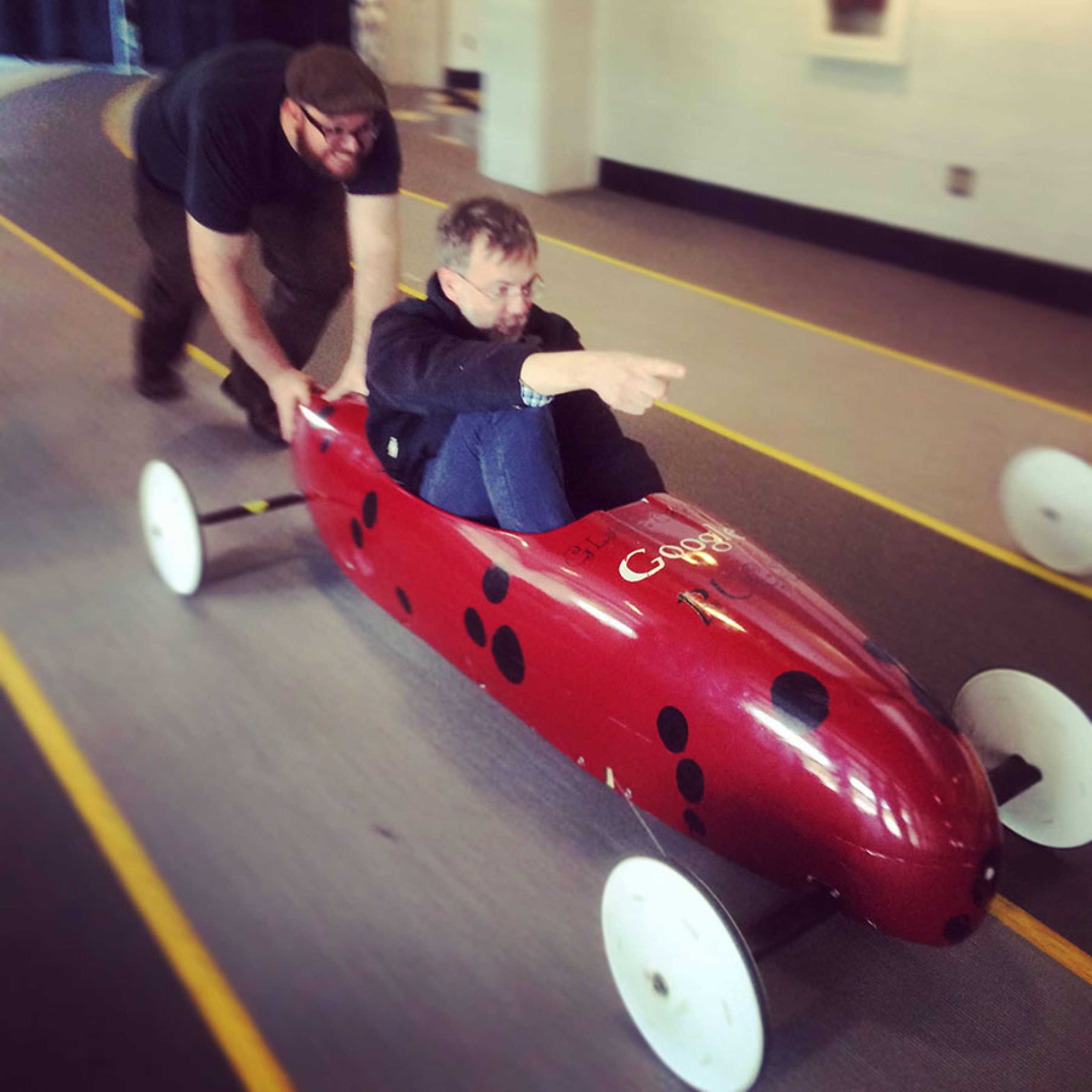 Josh White pushes Mark Nystrom in soap box derby car at STEAM Expo