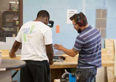Travis Donovan helps student in wood shop