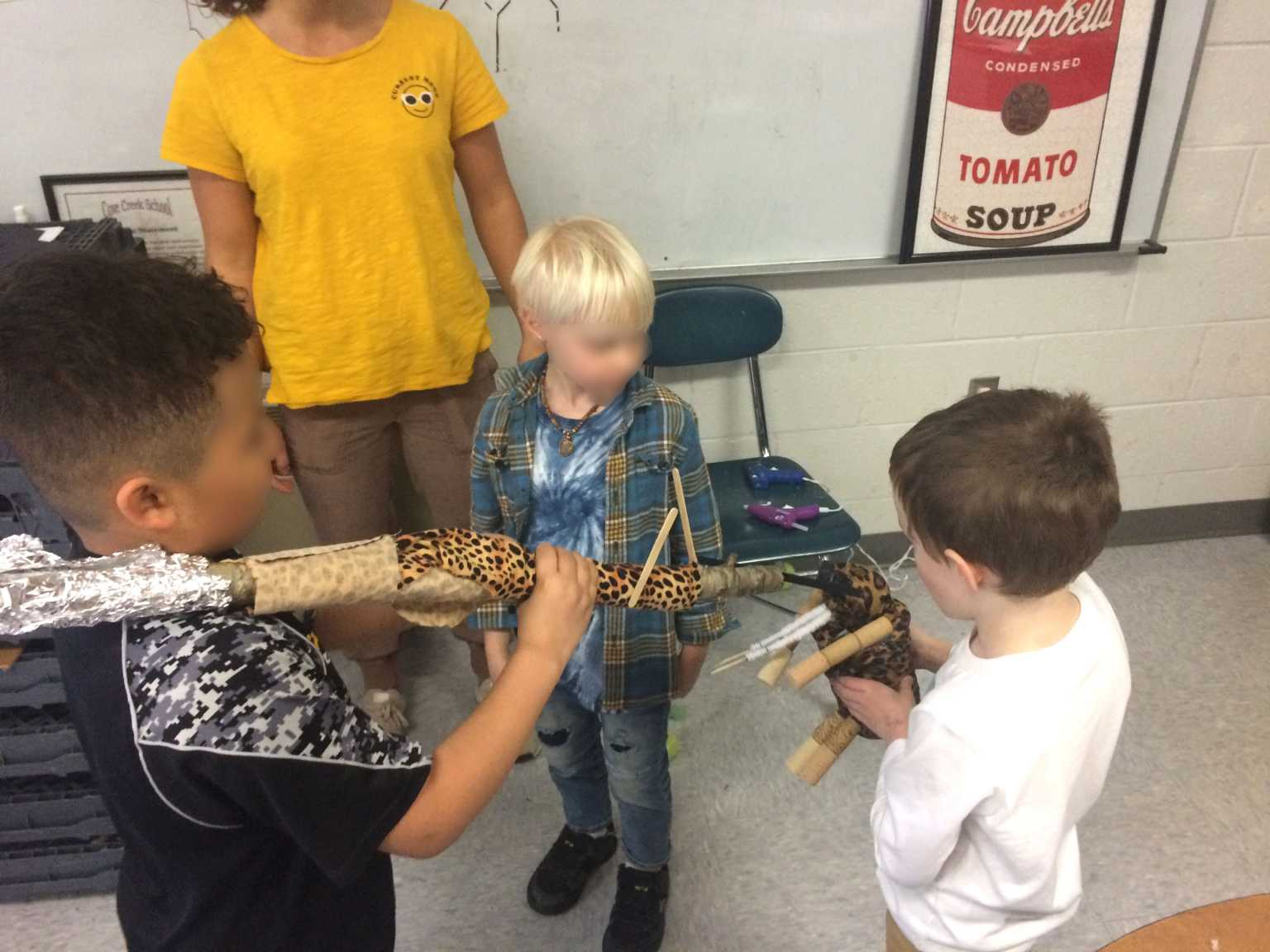 Elementary students create artwork with recycled materials.
