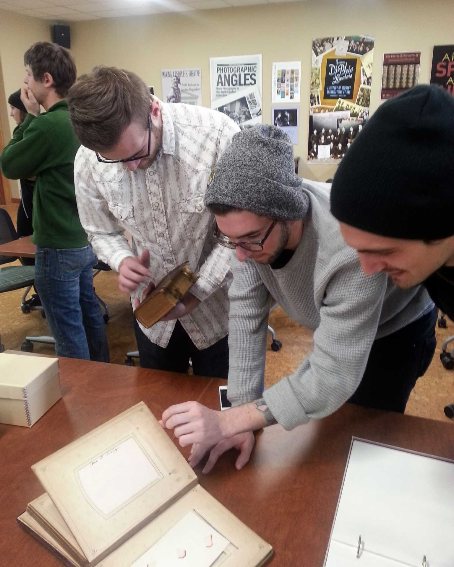 Students in the art history course, Photography and Culture, examine 19th century photographs in the Chapel Hill Wilson Library Special Collections.