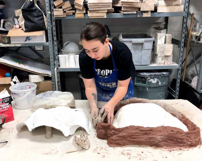 Sope Kahn working in clay studio